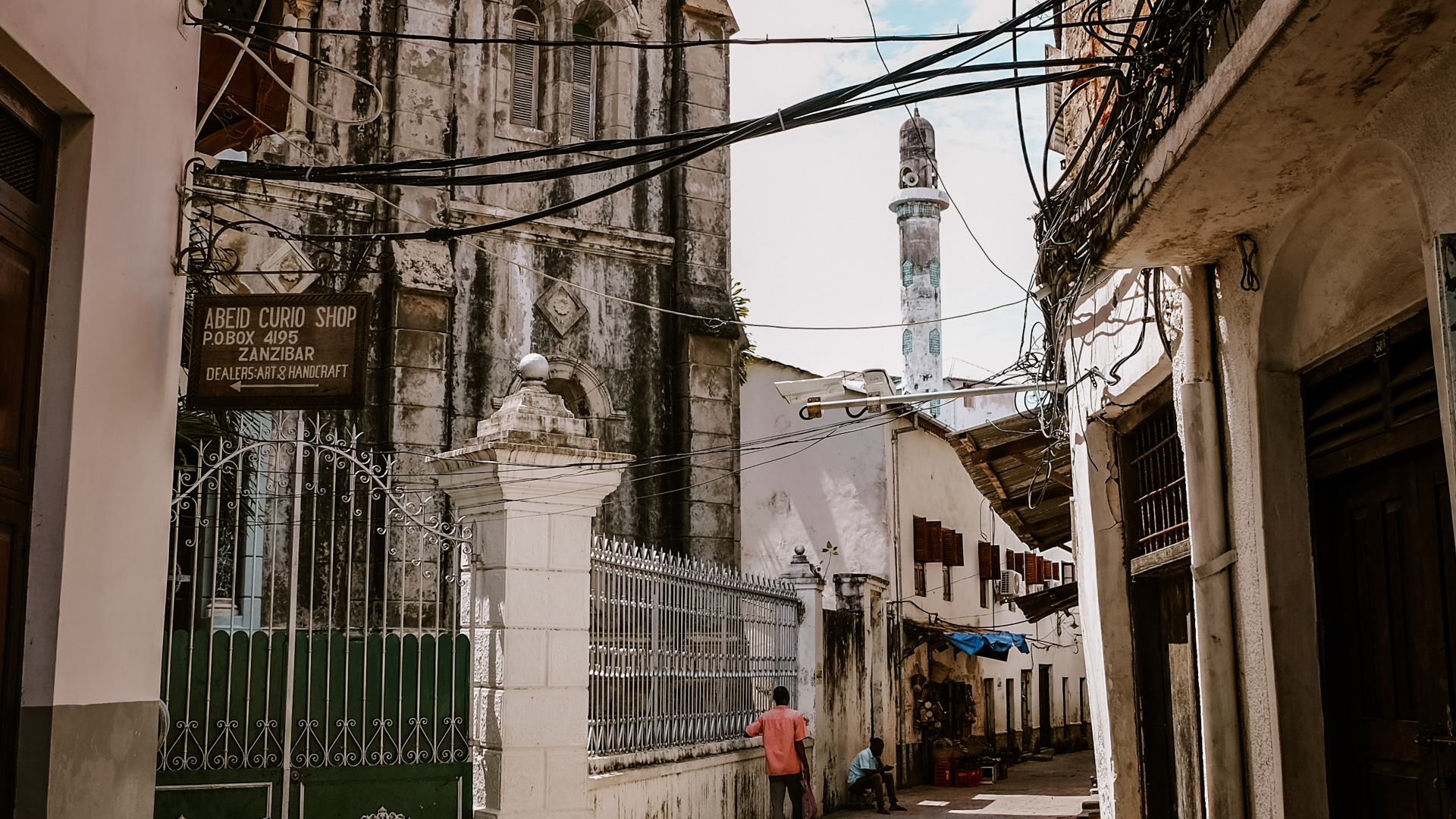 An alley next to Saint Joseph's Cathedral with the Istiqama mosque minaret in the background in Stone Town in Zanzibar, Tanzania